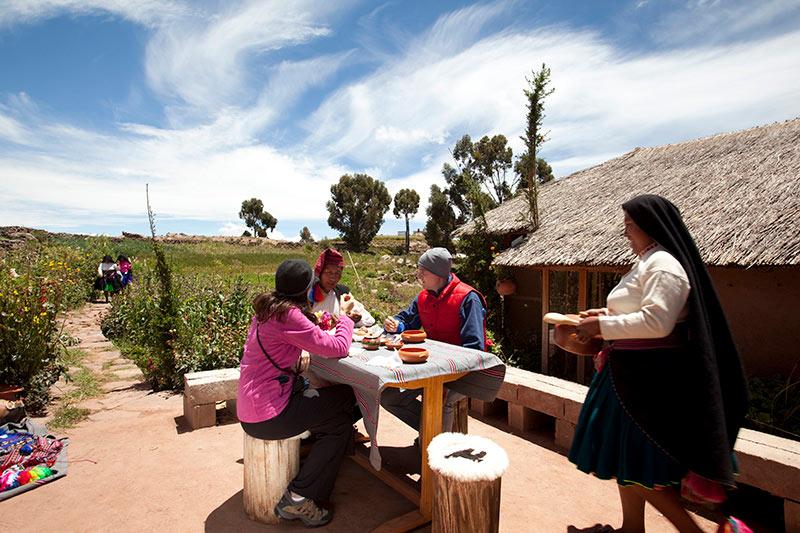 Turismo en el Perú. Pobladores le dan comida a turistas